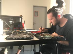Helpdesk - Un étudiant réparant un ordinateur